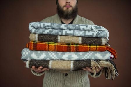Photo pour Image recadrée de l'homme tenant la pile de couvertures - image libre de droit