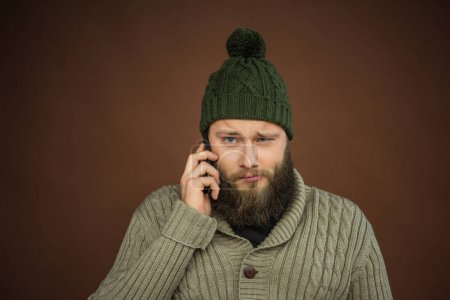 Photo for Man in green hat talking by smartphone - Royalty Free Image