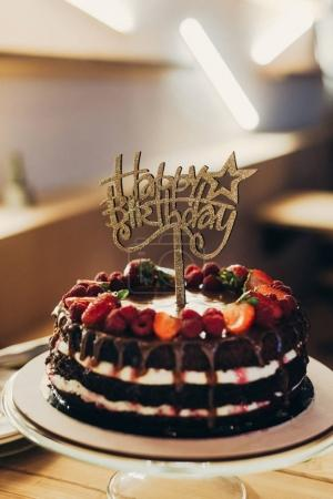 Photo for Happy Birthday sign on chocolate cake with fruits - Royalty Free Image