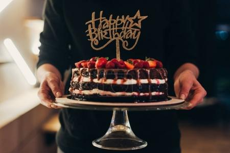 Photo for Cropped image of woman holding cake stand with chocolate cake - Royalty Free Image