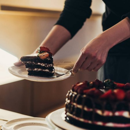 Photo for Cropped image of woman putting piece of homemade chocolate cake on plate - Royalty Free Image