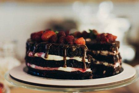 Photo pour Gros plan de gâteau au chocolat appétissant avec des fruits sur une table en bois - image libre de droit