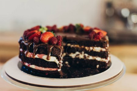 Photo for Delicious homemade chocolate cake with fruits on a wooden table - Royalty Free Image