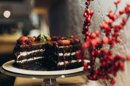 Photo for Chocolate cake on cake stand and twigs with berries in vase - Royalty Free Image