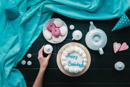 woman putting cupcake on birthday table