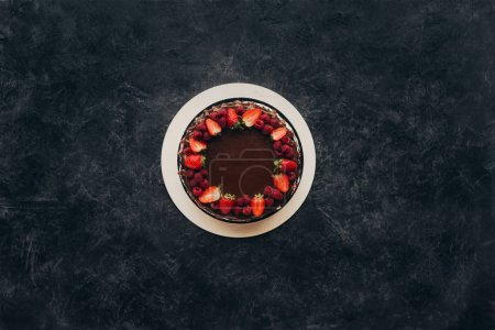 Photo for Top view of chocolate cake with strawberries and raspberries on gray surface - Royalty Free Image
