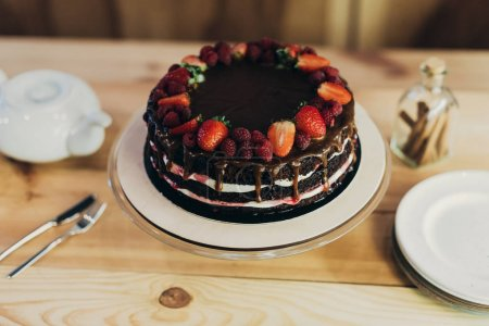 Photo for Appetizing chocolate cake with berries on a wooden table - Royalty Free Image