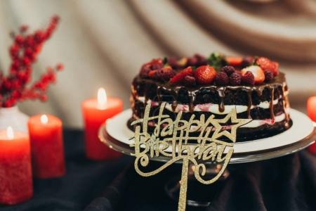 Photo for Happy birthday cake with candles on a table - Royalty Free Image