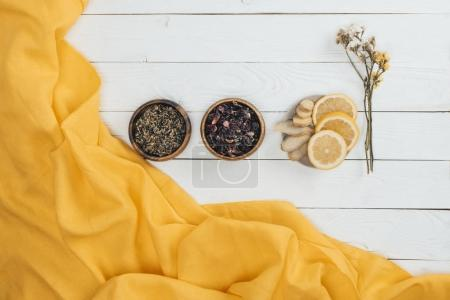 Photo for Top view of dry tea in bowls and sliced lemon with ginger on wooden table - Royalty Free Image