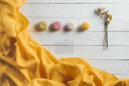 Photo for Top view of sweet delicious macaroons and flowers on wooden table - Royalty Free Image