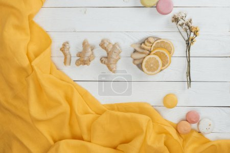 Photo for Top view of lemon, ginger and macarons on wooden table - Royalty Free Image