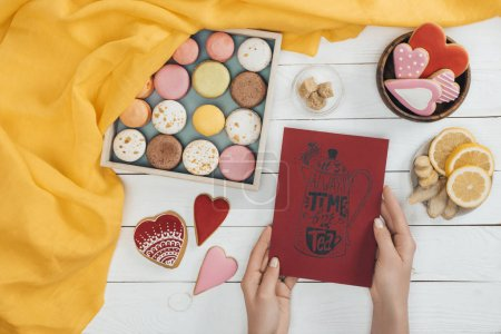 Photo for Top view of female hands holding tea card above wooden table with delicious macarons and heart shaped cookies - Royalty Free Image