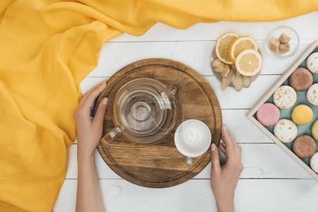 Photo for Top view of female hands holding cutting board with teapot and empty cup above wooden table with tasty macaroons - Royalty Free Image