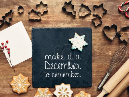"""Photo for Top view of forms and delicious gingerbread cookies on wooden table and """"Make it a December to remember"""" lettering on stone board - Royalty Free Image"""