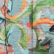 Back view of man painting colorful graffiti on wal...