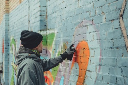 Photo for Male street artist painting colorful graffiti on wall - Royalty Free Image
