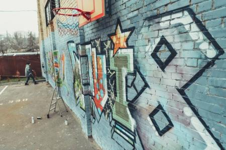 man painting colorful graffiti on wall with basketball hoop