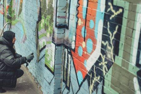 Photo pour Peinture colorée graffiti sur mur homme - image libre de droit