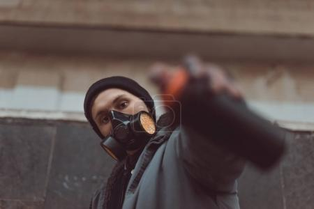 Photo for Selective focus of street artist in respirator holding can with spray paint - Royalty Free Image