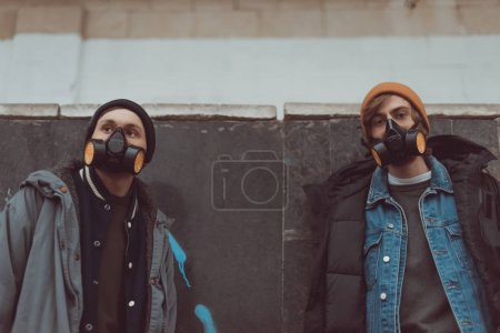 street artists in respirators standing at wall