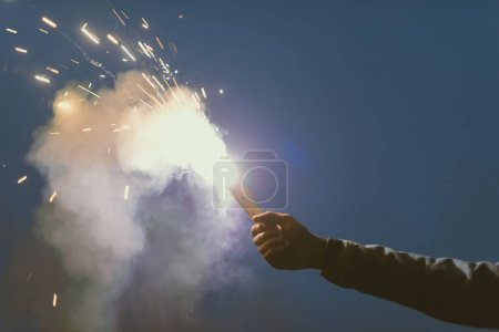 Photo for Cropped view of male hand with smoke bomb with sparks at night - Royalty Free Image