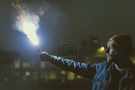 man holsing smoke bomb with sparks at night