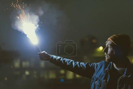 Foto de Bomba de humo hombre holsing con chispas en la noche - Imagen libre de derechos