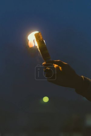 cropped view of male hand with smoke bomb with fire at night