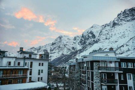 modern austrian town in mountains under sunset sky