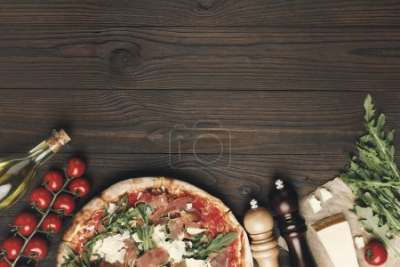 flat lay with italian pizza and various ingredients on wooden tabletop