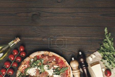 Photo pour Plat avec pizza italienne et divers ingrédients sur table en bois - image libre de droit