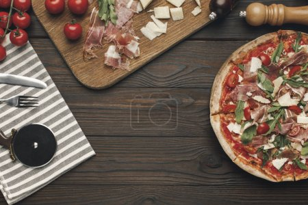 flat lay with arranged italian pizza, cutlery and various ingredients on wooden surface