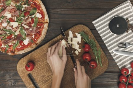 partial view of woman cutting cheese while cooking homemade italian pizza