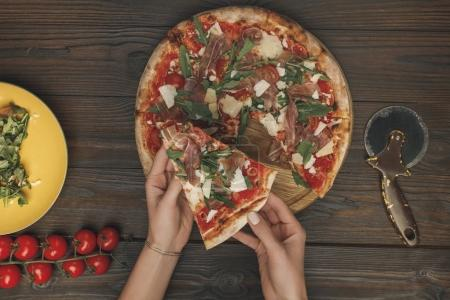 Photo for Partial view of female hands and homemade italian pizza on wooden surface - Royalty Free Image