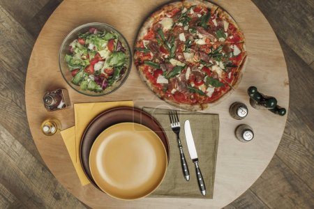 top view of arrangement of empty plates, pizza and salad on wooden table