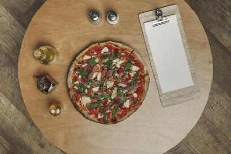 top view of arrangement of italian pizza, spices and various types of oil in bottles on wooden tabletop
