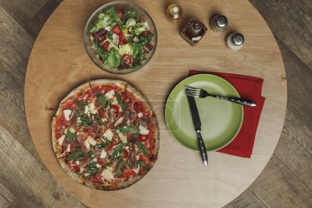top view of arrangement of salad in bowl, italian pizza and dinnerware on wooden table