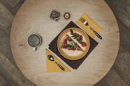 Photo pour Lay plat avec morceau arrangé de pizza sur la plaque, tasse de thé et de couverts sur table en bois - image libre de droit