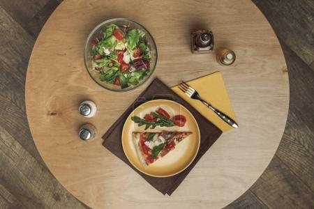 top view of piece of pizza on plate, salad in bowl and spices on wooden surface