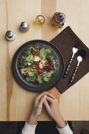 Photo for Cropped shot of female hands, salad in bowl, spices and cutlery on wooden tabletop - Royalty Free Image