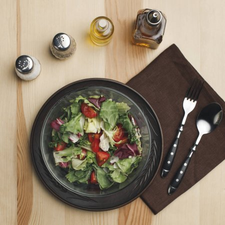 Photo for Flat lay with arranged salad in bowl, spices and bottles of oil on wooden surface - Royalty Free Image