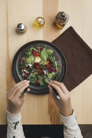 Photo for Partial view of woman mixing salad in bowl at wooden table - Royalty Free Image