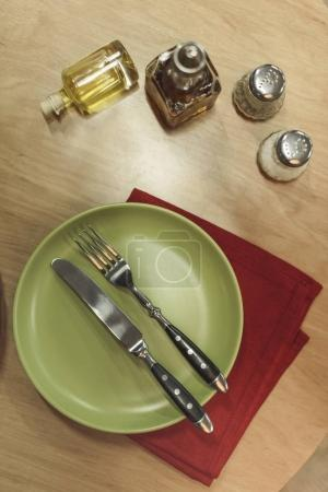 top view of arranged cutlery, napkin and spices on wooden surface
