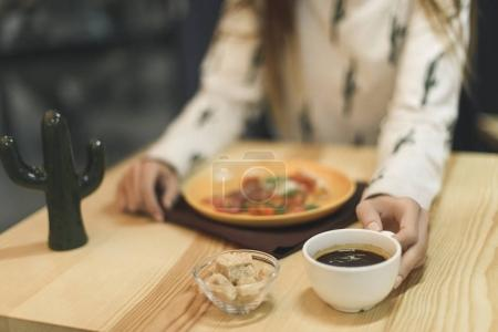 selective focus of woman sitting at table with cup of coffee and pizza piece on plate