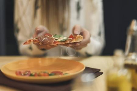 partial view of woman holding piece of italian pizza in hands