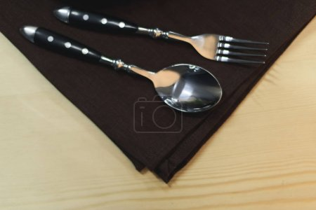 close up view of steel fork and spoon on napkin on wooden tabletop
