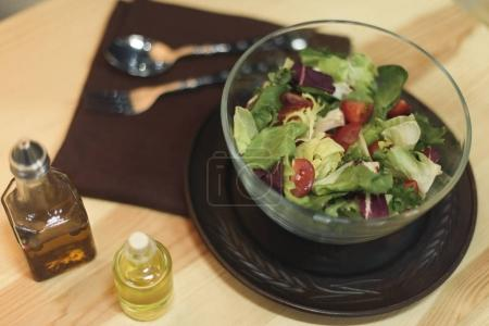 Photo for Close up view of fresh salad in bowl and oil in bottles on wooden surface - Royalty Free Image