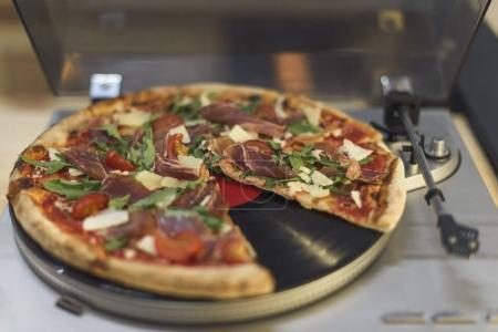 close up view of italian pizza on retro vinyl record player