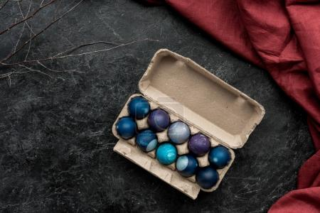 Painted eggs in egg carton on dark background