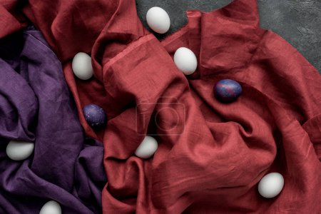 White and colored chicken eggs on textile background